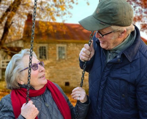 assisted living, elderly woman swinging and talking to elderly man